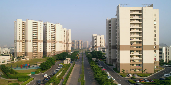 vatika gurgaon 21 three high rise towers with a road in between with green landscapes around