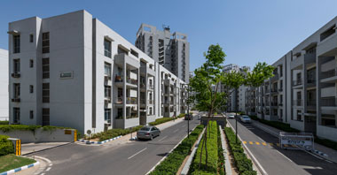 a roadside view of boulevard residences with boulevard heights in the background a project in vatika inxt by vatika group