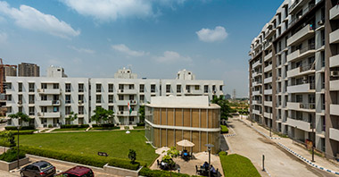 """a view of landscaped garden & buildings of vatika city homes in vatika inxt a project by vatika group"