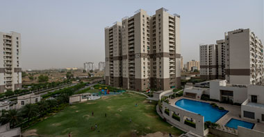 a view of landscaped garden & buildings of gurgaon 21 in vatika inxt a project by vatika group