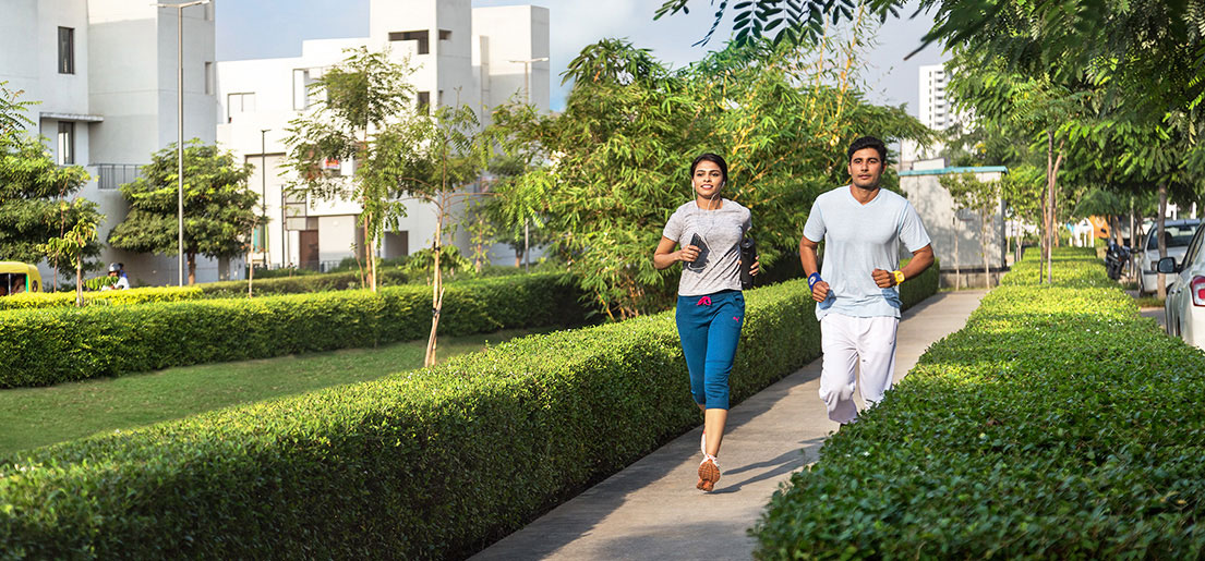 man and woman jogging on walkways in a gated community in vatika india next by vatika group