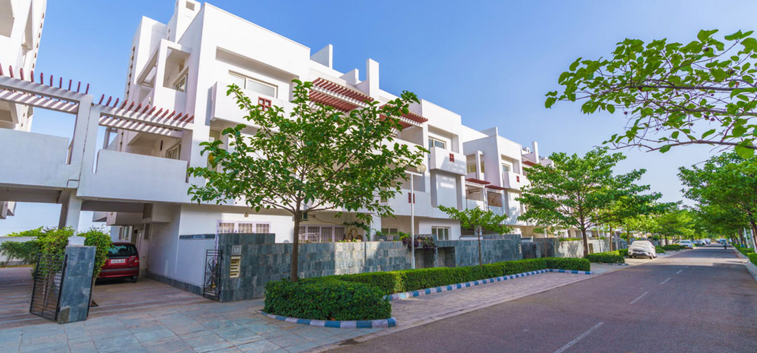 front side view of signature villa and walkways on the side of road in vatika india next by vatika group